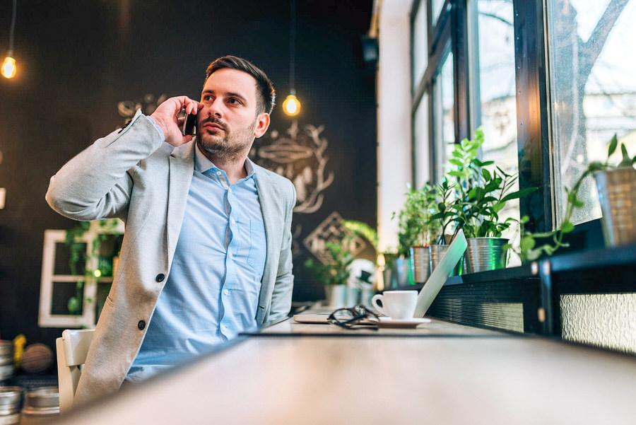 logiciel comptable Agent commercial immobilier homme répond au téléphone